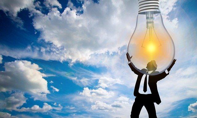 muž držící obří rozsvícenou žárovku